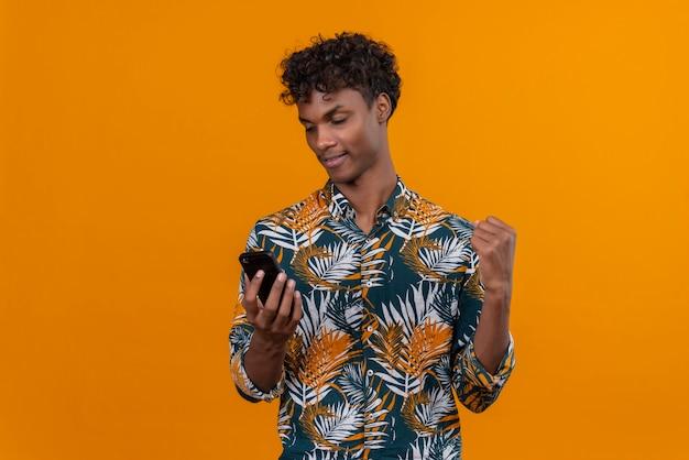 Ein junger gutaussehender dunkelhäutiger mann mit lockigem haar in einem mit blättern bedruckten hemd, das kraftgeste mit armen zeigt