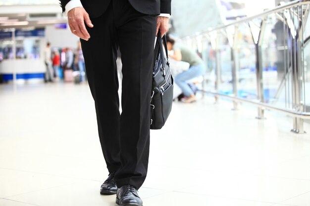 Ein junger gutaussehender geschäftsmann student in einem anzug kommt mit einer aktentasche am bahnhof, flughafen. konzept - ein neues geschäft, die welt bereisen, kommunikation, kontakte, ein neues geschäft, erfolg, spaziergang.