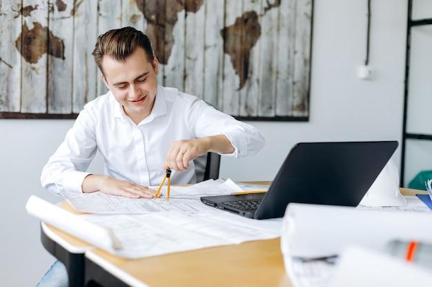 Ein junger gutaussehender mann, der glücklich an einer zeichnung in seinem büro arbeitet