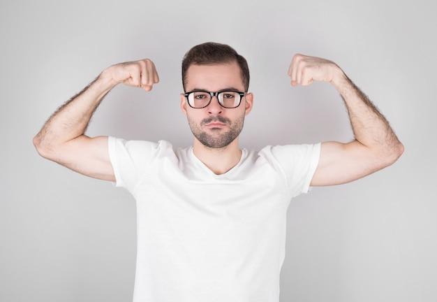 Ein junger gutaussehender mann in einem t-shirt an einer grauen wand ist ein starker mann, der die muskeln seiner arme zeigt, selbstbewusst und stolz auf seine stärke