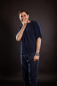 Ein junger gutaussehender mann lacht ansteckend und bedeckt seinen mund mit seiner hand. schwarzer hintergrund