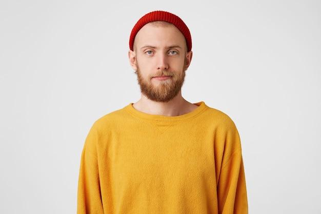 Ein junger gutaussehender mann mit bart und blauen augen steht mit einem gleichgültigen, unzufriedenen, apathischen gesicht da
