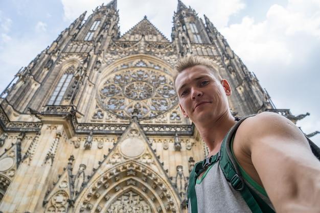 Ein junger, gutaussehender mann mit blauem purpur macht ein selfi im hintergrund der st.-veits-kathedrale. prag