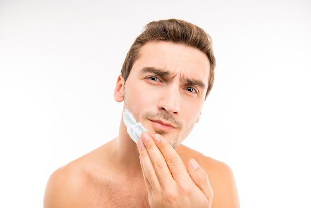 Ein junger gutaussehender mann rasiert sich vor der kamera