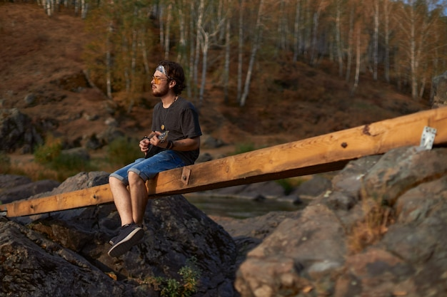 Ein junger hippie-mann in jeans-shorts und mit einem schal auf dem kopf sitzt auf einer brücke in der nähe der felsen und ...