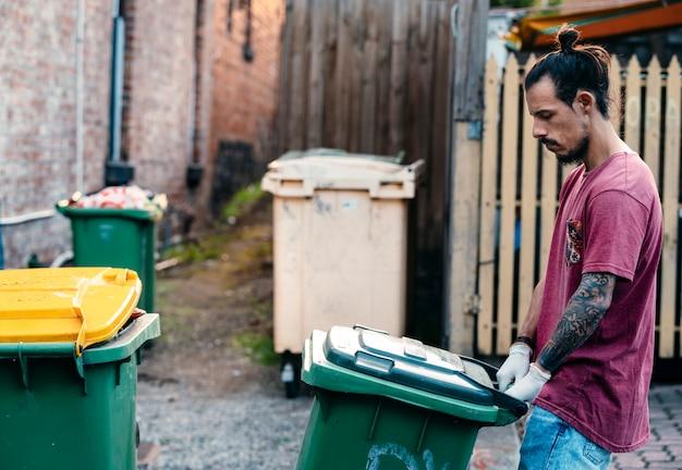 Ein junger hipster-mann, der sich sorgen um die umwelt macht, schiebt die vollen mülltonnen auf die straße, um sie abzuholen