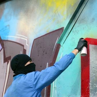 Ein junger hooligan mit verstecktem gesicht malt graffiti auf eine metallwand.