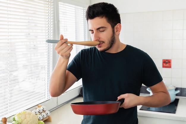 Ein junger hübscher brunettemann steht in der küche und hält eine bratpfanne in seinen händen. ehemann, der frühstück für seine frau zubereitet.