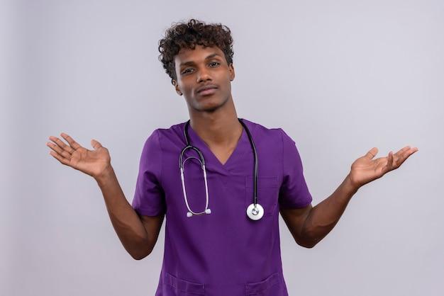 Ein junger hübscher dunkelhäutiger arzt mit lockigem haar in violetter uniform mit stethoskop, das hände mit verwirrtem ausdruck öffnet