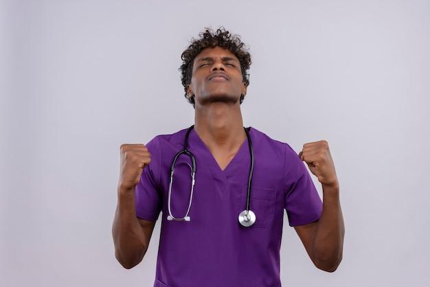 Ein junger hübscher dunkelhäutiger arzt mit lockigem haar in violetter uniform und stethoskop, der mit geballten fäusten die hände hebt