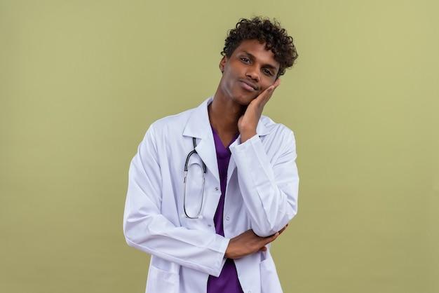 Ein junger hübscher dunkelhäutiger mann mit lockigem haar, der einen weißen kittel mit stethoskopschmerz trägt, während er seine zähne auf einer grünfläche berührt