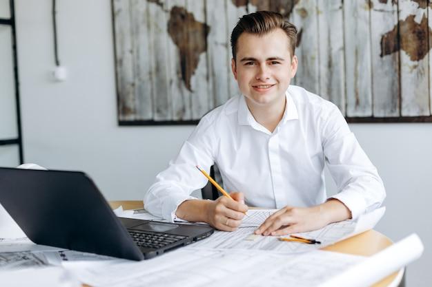 Ein junger hübscher geschäftsmann arbeitet an einem schreibtisch im büro