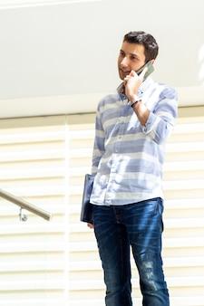 Ein junger hübscher mann der vorderansicht im gestreiften hemd, der arbeitsprobleme am telefon während des aufbaus der tagesarbeitsaktivität spricht und bespricht