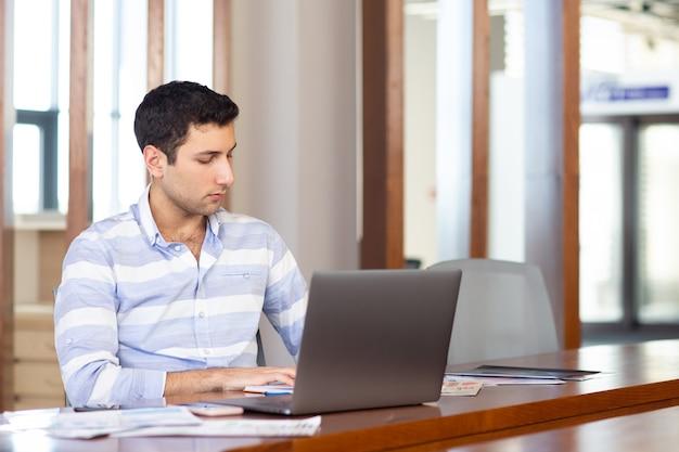 Ein junger hübscher mann der vorderansicht im gestreiften hemd, der innerhalb seines büros unter verwendung seines silbernen laptops während des tagesarbeitsaktivitätsaufbaus arbeitet