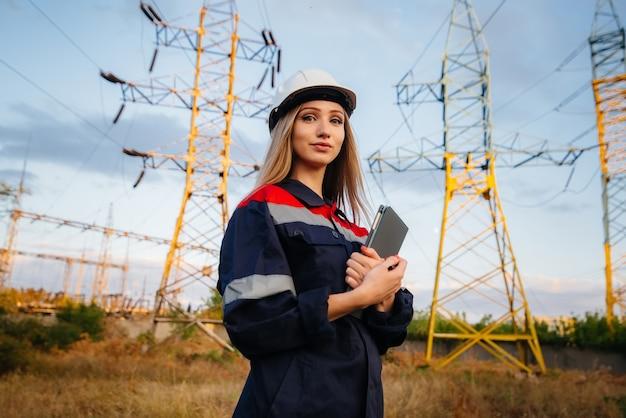 Ein junger ingenieur inspiziert und kontrolliert die ausrüstung der stromleitung