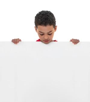 Ein junger junge, der weißes brett mit exemplar-platz anhält