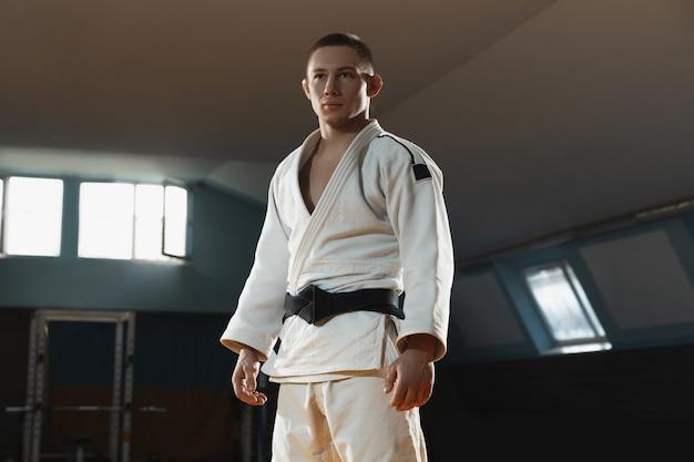 Ein junger kämpfer im kimono trainiert kampfkunst im fitnessstudio