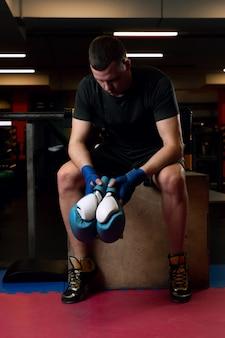 Ein junger kämpfer mit boxhandschuhen in den händen ruht nach dem training im fitnessstudio und lässt den kopf sinken.