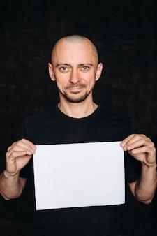 Ein junger kahlköpfiger mann mit einem leeren weißen laken. auf einem schwarzen hintergrund, in einem schwarzen t-shirt, hält eine person ein werbeblatt, einen kopienraum, isoliert