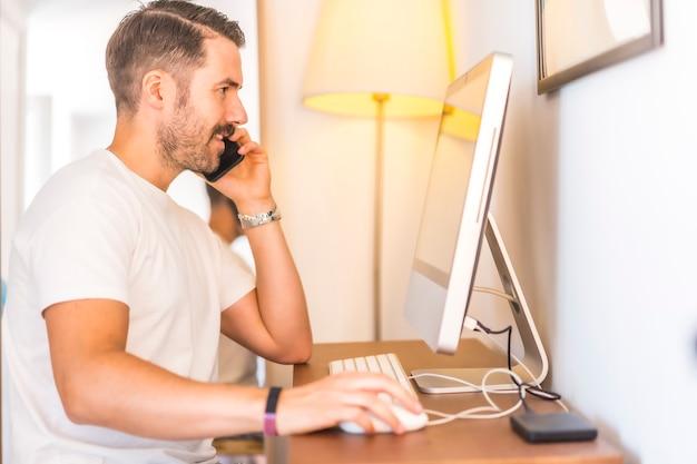 Ein junger kaukasischer mann, der zu hause am computer telearbeitete
