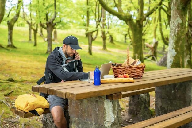 Ein junger kaukasischer vater, der mit seinem computer an einem picknicktisch sitzt und telefoniert, mit dem jungen in seinem rucksack