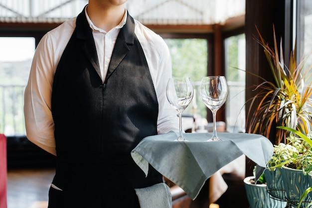 Ein junger kellner in stilvoller uniform steht mit gläsern auf einem tablett neben dem tisch in einem schönen gourmetrestaurant aus nächster nähe. restauranttätigkeit auf höchstem niveau.