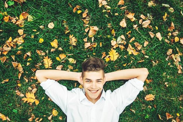 Ein junger kerl in einem weißen hemd liegt auf dem gras mit draufsicht des herbstlaubs.