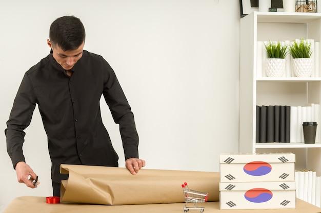 Ein junger koreanischer mann in einem büro packt eine postpaket-geschenkverlosung zum versenden.
