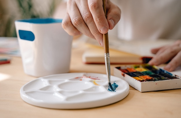 Ein junger künstler malt mit aquarellen in einem notizbuch, das an einem holztisch sitzt. schöne männliche hände halten eine bürste. nahaufnahme. sonnenstrahlen und angenehme atmosphäre. bastelkonzept.der künstler in aktion