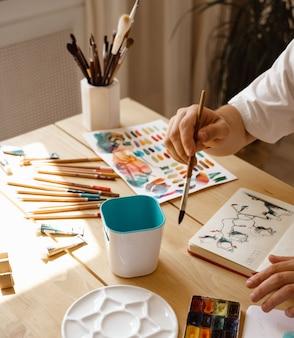 Ein junger künstler zeichnet aquarell und sitzt an einem holztisch. schöne männliche hände halten einen pinsel. nahaufnahme. sonnenstrahlen und angenehme atmosphäre. konzept diy. echter kunstmacher in aktion.
