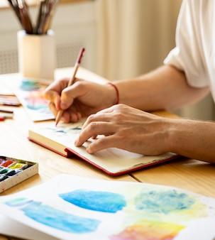 Ein junger künstler zeichnet ein notizbuch, während er an einem holztisch sitzt. schöne männliche hände halten einen farbigen bleistift. nahaufnahme. sonnenstrahlen und angenehme atmosphäre. konzept diy. echter kunstmacher in aktion