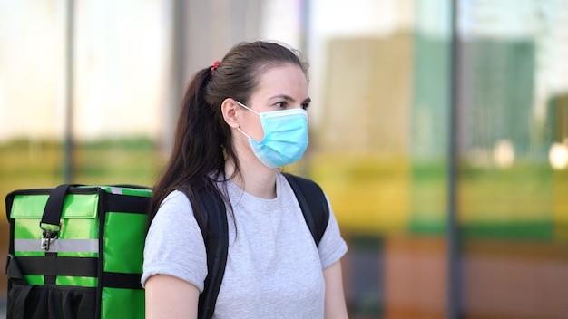 Ein junger kurier, der eine medizinische maske trägt, liefert die bestellung an die kunden