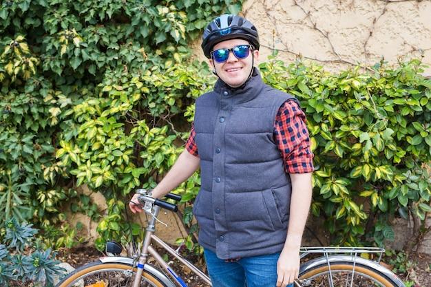 Ein junger lächelnder mann hält fahrrad im garten