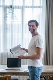 Ein junger lächelnder mann mit projektpapieren in den händen