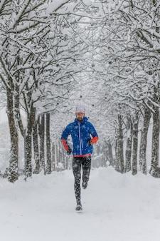 Ein junger läufer in einem mit schnee ausgekleideten boden