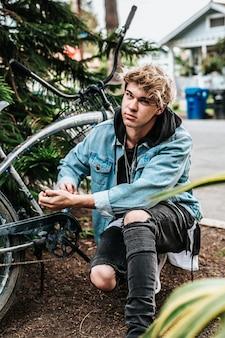 Ein junger lockiger blonder mann, der neben einem cruiser-fahrrad seine knie auf den boden legt