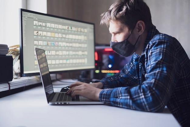 Ein junger männlicher arbeiter mit schutzmast im büro, der am tisch sitzt
