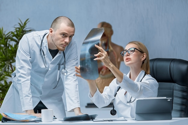 Ein junger männlicher arzt berät sich mit einem erfahreneren kollegen wegen einer röntgenaufnahme