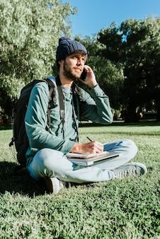 Ein junger männlicher blogger, der in seinen notizblock schreibt, genießt das digitale nomadenleben. er telefoniert mit seinen kunden und macht sich notizen. konzept: glück und freiheit