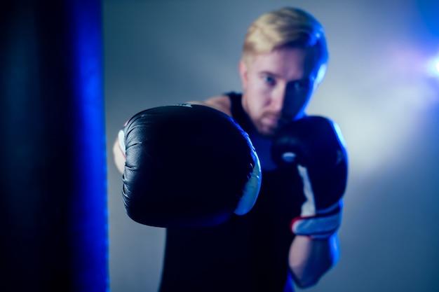 Ein junger männlicher boxer treibt sport in der turnhalle. boxer, boxhandschuhe auf dunklem hintergrund. mann schlägt zu