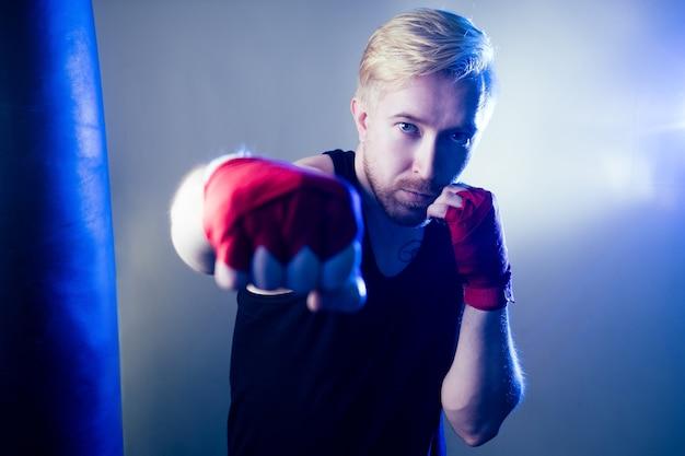 Ein junger männlicher boxer treibt sport in der turnhalle. boxer, zieht boxhandschuhe auf dunklem hintergrund an. der mann schlägt zu. roter verband an den händen