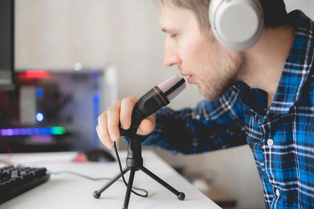 Ein junger männlicher hübscher moderator, der podcast im studio aufzeichnet und live streamt