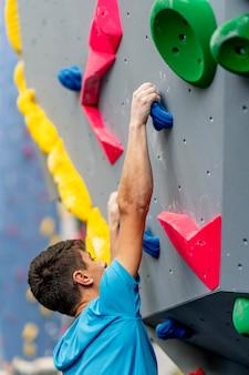 Ein junger männlicher kletterer, der das klettern auf einer kletterwand übt.