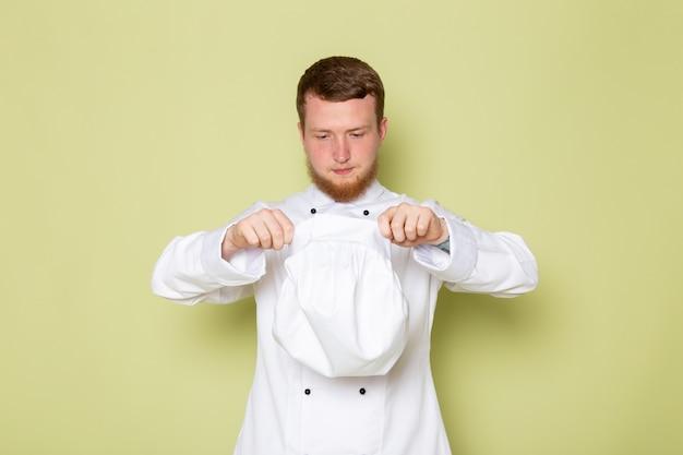 Ein junger männlicher koch der vorderansicht im weißen kochanzug, der seine weiße kappe abzieht