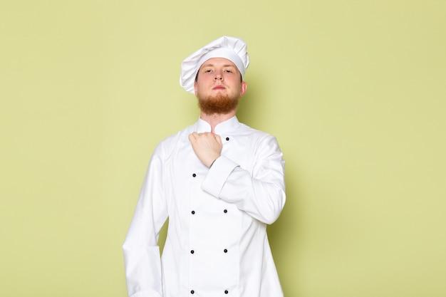 Ein junger männlicher koch der vorderansicht im weißen kochanzug weiße kopfkappe, die sein tuch fixiert