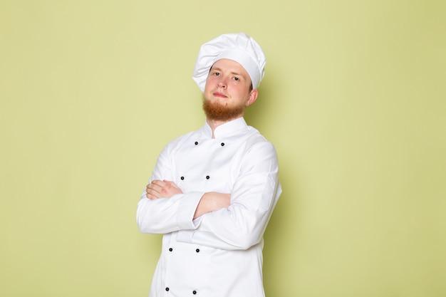 Ein junger männlicher koch der vorderansicht in der weißen kopfkappe des weißen kochanzugs aufwerfend