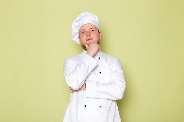 Ein junger männlicher koch der vorderansicht in der weißen kopfkappe des weißen kochanzugs, der das denken aufwirft