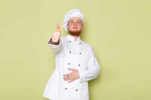 Ein junger männlicher koch der vorderansicht in der weißen kopfkappe des weißen kochanzugs, der fantastisches zeichen zeigt