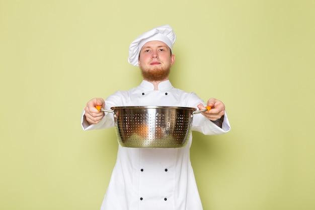 Ein junger männlicher koch der vorderansicht in der weißen kopfkappe des weißen kochanzugs, der silbernen topf hält