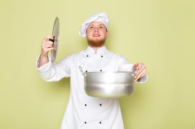 Ein junger männlicher koch der vorderansicht in der weißen kopfkappe des weißen kochanzugs, der silbernen topf lächelnd hält